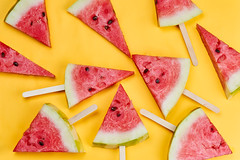 Organic watermelon slices with sticks on bright yellow background