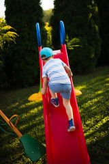 Young boy climbing on the slide.