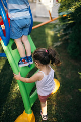 Young boy and girl climbing on the slide.