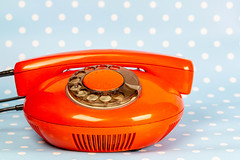 Vintage red telephone on blue background