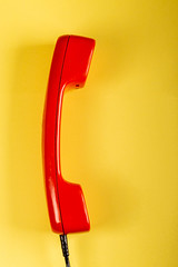 Red phone receiver on yellow background