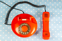 Top view of red vintage phone with handset on blue background