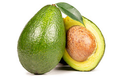Avocado with a green leaf on a white background