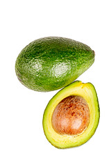 Whole and half avocado on a white background