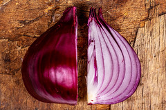 Cut purple onion on an old wooden background, top view