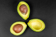 Three halves of an avocado on a black background, top view