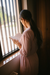 Young woman reading a book near window at the morning.