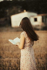 Glamour girl in vintage dress reading a book in nature.