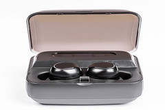 Small wireless headphones in box on white background