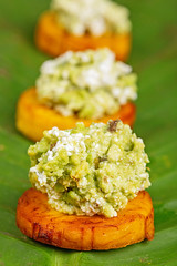 Appetizer with avocado and plantain on a green leaf, close-up