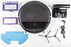 Top view, robot vacuum cleaner and set of its accessories on white