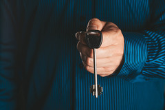 A man in a blue shirt holds a key in his hand