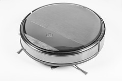 The automated robot vacuum cleaner of a roundish form on white