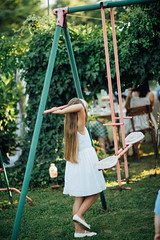 Young blonde girl with long hair and white dress standing on the playground in the backyard.