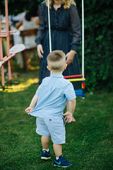 Young boy and his mother standing near the swing in the backyard.
