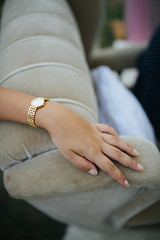 Girl's hand with golden watch resting on the armchair.