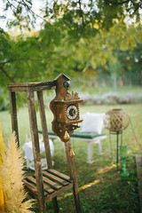 Old vintage clock on the wooden stand in the backyard.