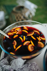 Punch with blueberries and lemon in a glass bowl.