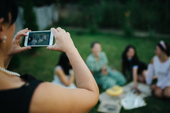 Woman taking a picture of her friends with mobile phone.