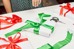 Woman decorating Xmas present with colorful ribbons