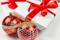 Christmas ornaments and beautiful present box bowed with red textile ribbon