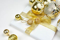 Pile of golden Christmas tree ornaments and present box wrapped in white paper