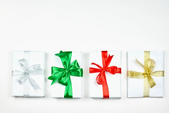 A straight row of four simple paper wrapped Christmas presents with colorful bows