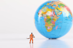 Miniature worker with globe on white background