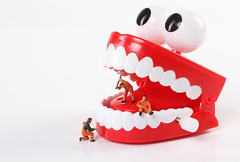 Miniature people cleaning teeth on white backgroudn