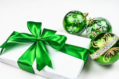 Simple classic wrapped gift box with green ribbon bow and festive holiday decorations