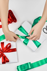 Woman wrapping beautiful Christmas gift in the white paper