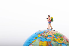 Miniature traveler with backpack on globe