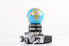 Miniature travelers with vintage camera and globe on white background