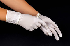 White latex medical gloves on a woman's hands on dark background