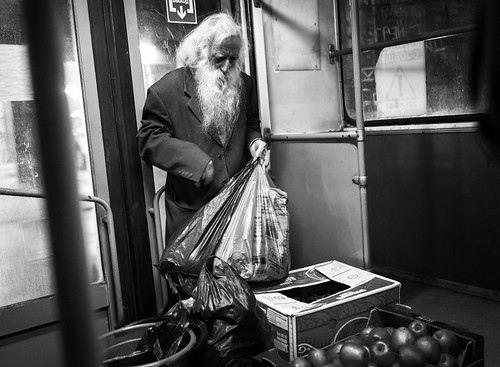 old man with apples in a night bus