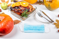 Thanksgiving background with fried chicken, pumpkin, leaves, cutlery and medical mask