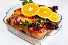 Delicious whole roasted chicken with orange in glass baking sheet, close up