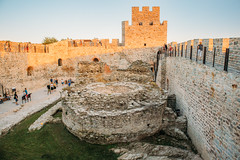 Tourists standing near the stone building inside the Ram fortress walls