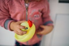 Young girl holding yellow rubber duck in her hand.