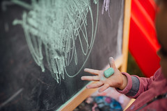 Young girl in front of the chalkboard holding a green chalk in her hand.