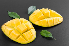 Halves of the mango with green leaves on black