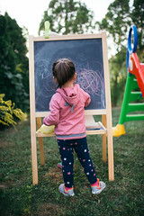 Young girl drawing on the chalkboard in the backyard.