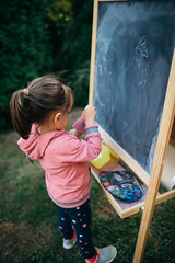Young girl standing in front of the chalkboard in the backyard.