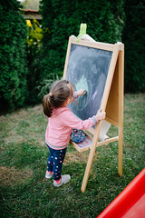 Girl drawing on the chalkboard in the backyard.
