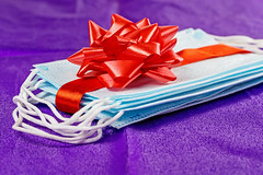 Masks as a gift, tied with a red ribbon with a bow on a purple background