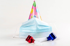 Hat in the form of a cone with medical mask. Birthday celebration during quarantine