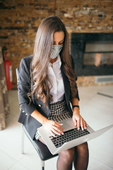 Young businesswoman with protective mask typing on laptop in her modern office.