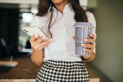 Woman with pepito suit using smartphone and drinking coffee.