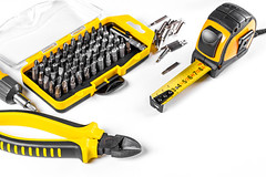 Wire cutters, set of bits, tape measure and screwdriver on white
