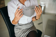 Woman putting a face mask on her face in the office.